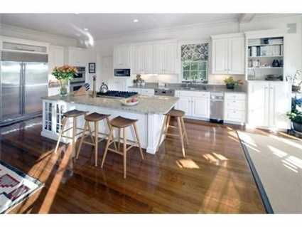 Check out the large family kitchen with island, fireplace and French doors to terrace.
