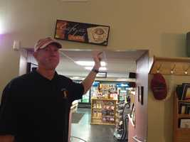 Bob Farwell shows a sign shaken by quake in Hollis Center, Maine