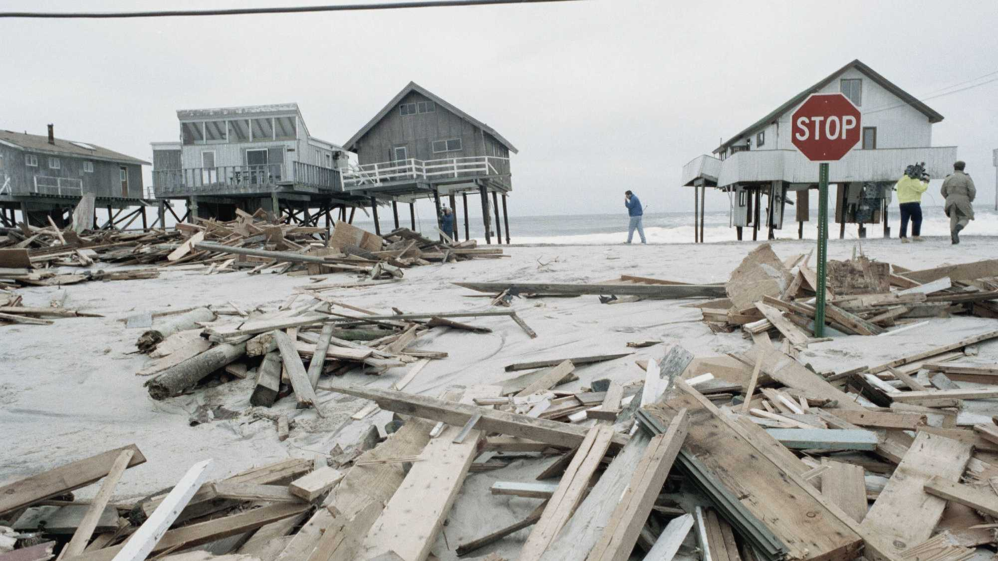 People survey the damage to home along Westhampton Beach after strong winds and high tides swept across the region.