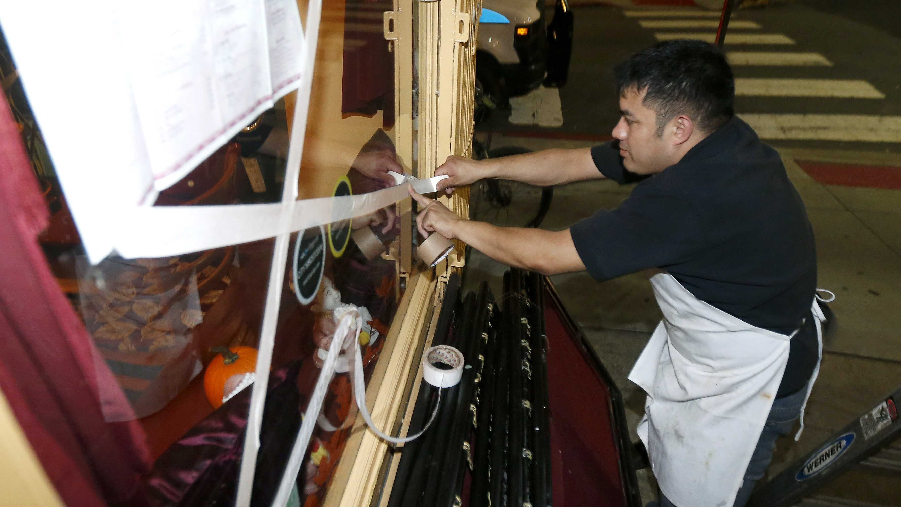Oswaldo Falleres puts tape on the window of a restaurant in preparation for the arrival of superstorm Sandy, Sunday, Oct. 28, 2012, in Hoboken, N.J.