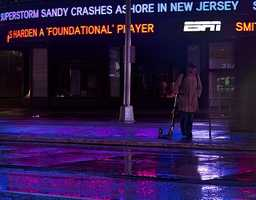 A lone pedestrian stand with his scooter near a message about superstorm Sandy in New York's Times Square, early Tuesday, Oct. 30, 2012.