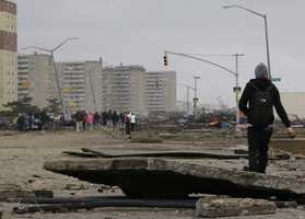 Pedestrians asses the damage from flooding near Rockaway Beach in the New York City borough of Queens in the aftermath of superstorm Sandy, Tuesday, Oct. 30, 2012, in New York.