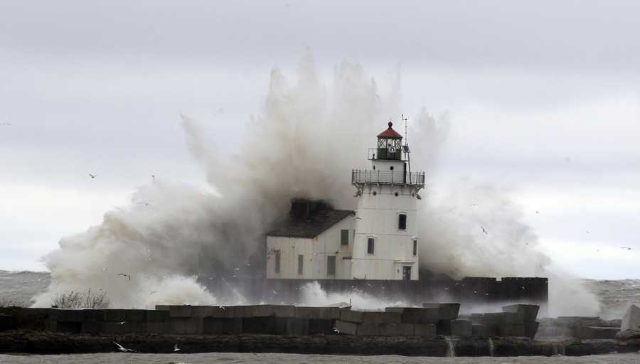 Waves pound a lighthouse on the shores of Lake Erie Tuesday, Oct. 30, 2012, near Cleveland. High winds spinning off the edge of superstorm Sandy took a vicious swipe at northeast Ohio early Tuesday, uprooting trees, cutting power to hundreds of thousands, closing schools and flooding parts of major commuter arteries that run along Lake Erie.