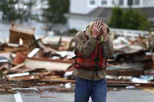 Brian Hajeski, 41, of Brick, N.J., reacts after looking at debris of a home that washed up on to the Mantoloking Bridge the morning after superstorm Sandy rolled through, Tuesday, Oct. 30, 2012, in Mantoloking, N.J. Sandy, the storm that made landfall Monday, caused multiple fatalities, halted mass transit and cut power to more than 6 million homes and businesses.