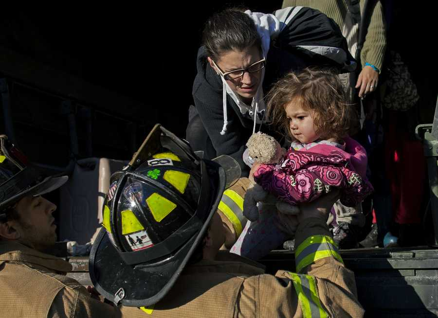 On a National Guard truck, Ali LaPointe, of Hoboken, N.J., hands her daughter Eliza Skye LaPointe, 18-months-old, to Hoboken firefighters, Wednesday, Oct. 31, 2012, in Hoboken, N.J., in the wake of superstorm Sandy. Some residents are being plucked from their homes by large trucks as parts of the city are still covered in standing water.