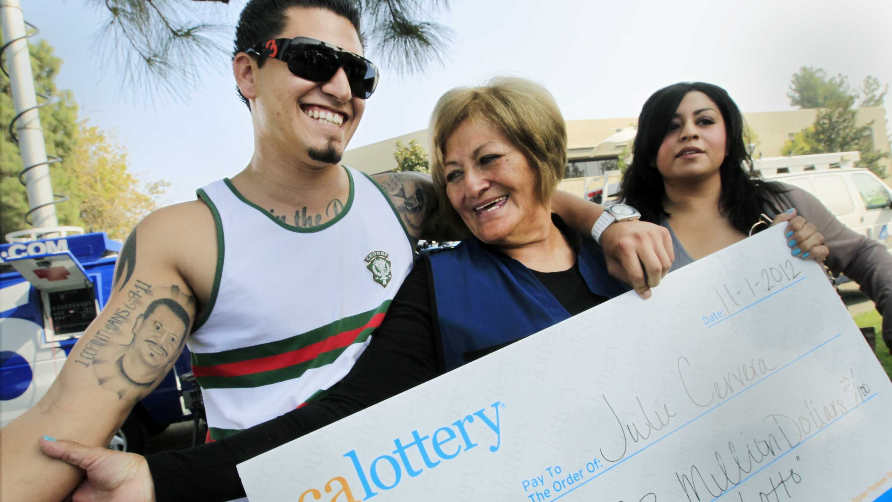 Lottery winner Julie Cervera, center, looks at her recently dead son pictured on a tattoo, as she is hugged by her grandson Rudy Ray, left, and daughter Charliena Marquez, right. The 69-year-old California grandmother came forward to claim a $23 million lottery jackpot after the winning ticket languished in her car's glove compartment for months and almost expired.