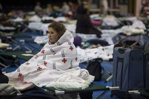 Kaitlyn Miller, 15, keeps herself warm with a blanket from the Red Cross at the Pinebelt arena in Toms River, N.J.