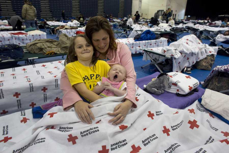 Candice Haugland of Seaside Heights, N.J., and her niece, eight-year-old Amy Hoopingarner and two-month-old Nora Remington, are settling in at the Red Cross shelter in the Pine Belt Arena in Toms River, N.J. A steady flow of evacuees has been filling the shelter since Sunday&#x3B; shelter capacity is 1,100.
