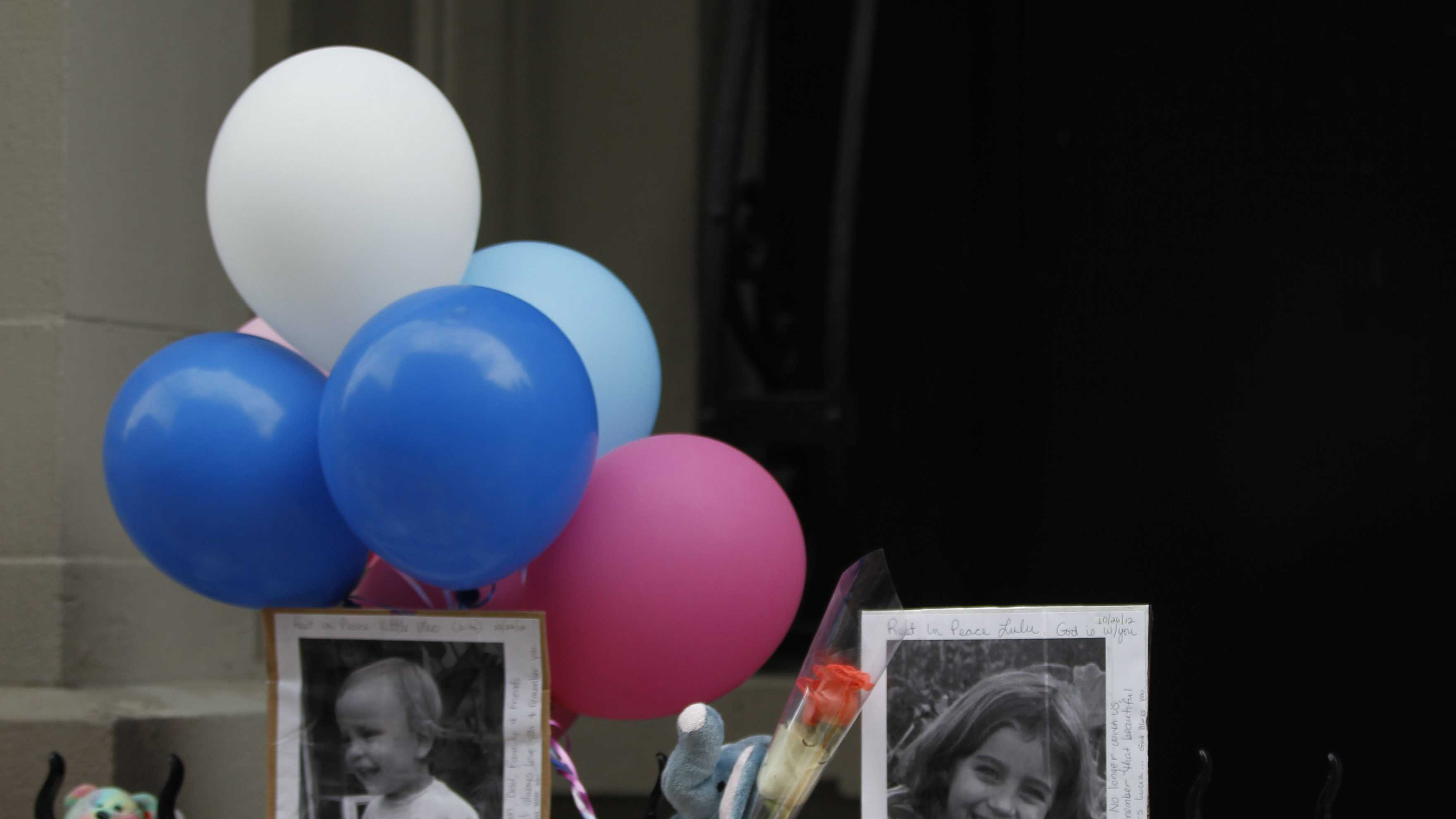 Photographs of the two children allegedly stabbed by their nanny are displayed alongside balloons and stuffed animals at memorial outside the apartment building were they lived.