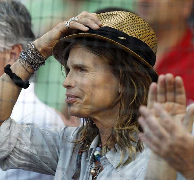 Steven Tyler, lead singer of Aerosmith, adjusts his hat prior to watching a baseball game between the Boston Red Sox and the New York Yankees at Fenway Park in Boston, Friday, Aug. 5, 2011.