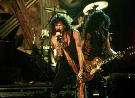 Members of the rock group Aerosmith, from left, Steven Tyler and Joe Perry, using a Les Paul guitar, perform during the 36th Annual Grammy Awards at New York's Radio City Music Hall, Tuesday night, March 1, 1994.