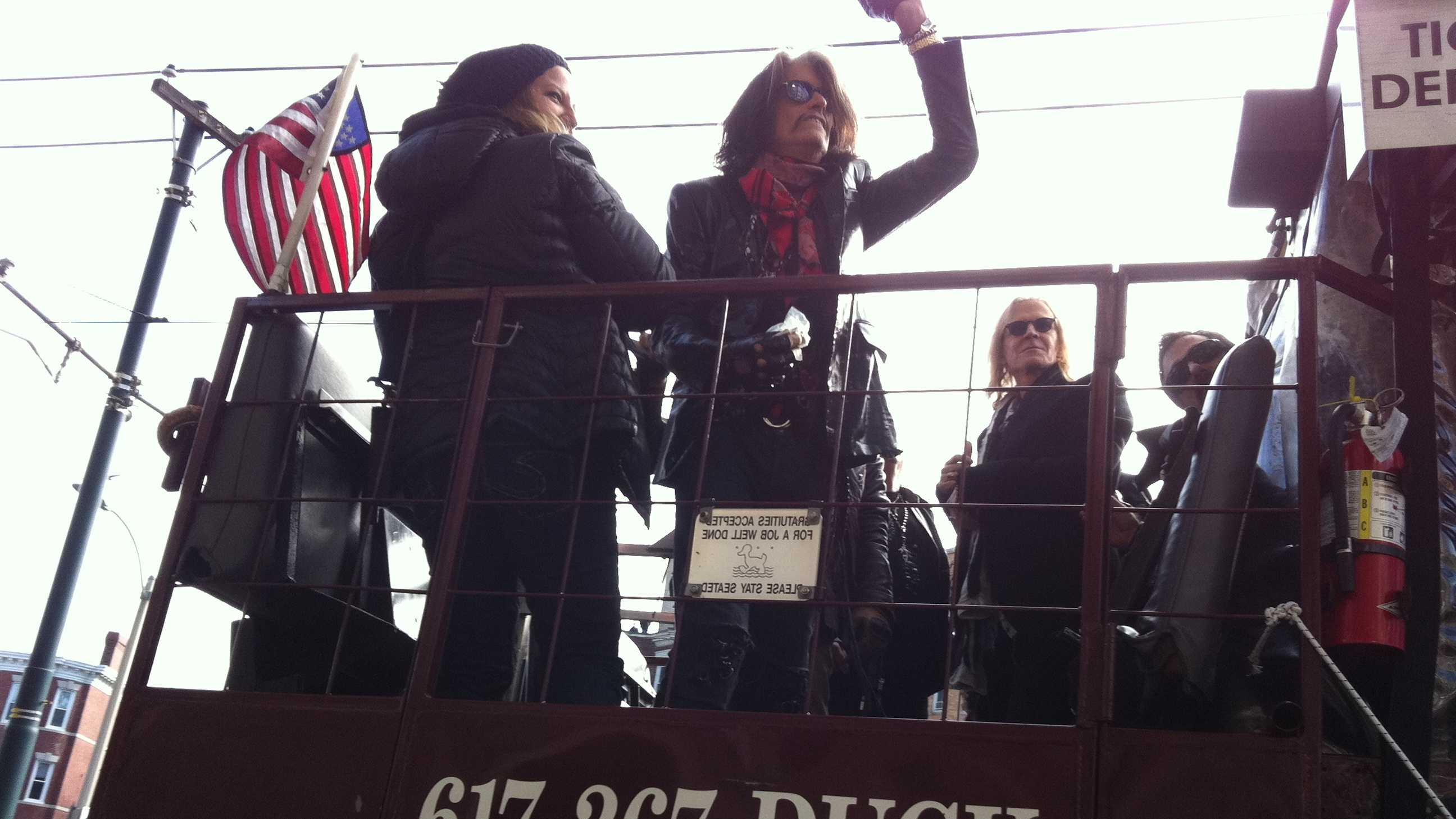 Guitarist Joe Perry waves to the crowd from a duckboat.