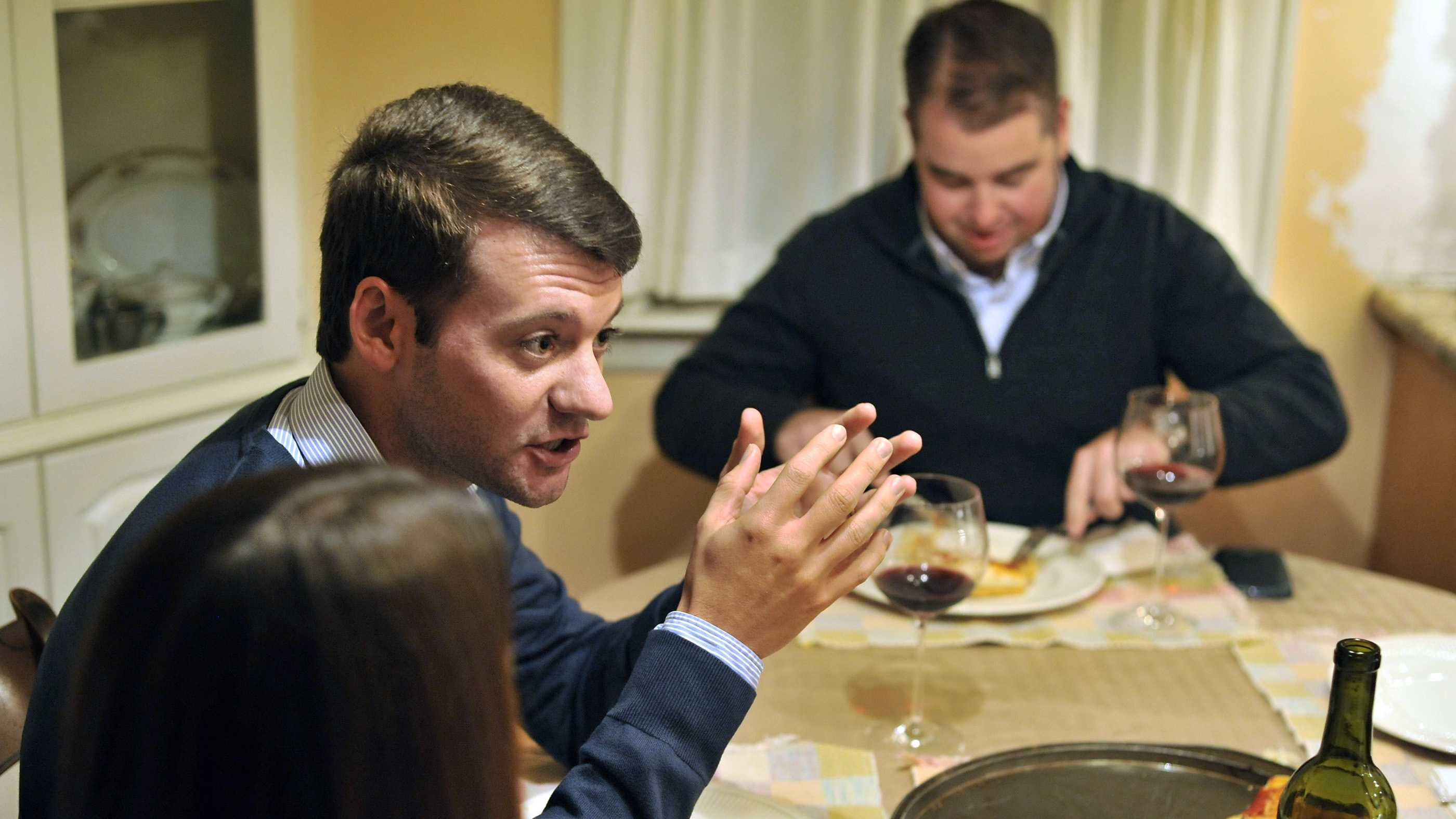 Brian Malone, of Duxbury Mass., speaks about the recent presidential election, while gathered with his extended family including his wife Rebecca Malone, left, and brother-in-law Andrew Marshall, right, of Quincy Mass., during dinner at his in-law's house in Hingham, Mass., where politics is a frequent, and divisive topic of conversation.