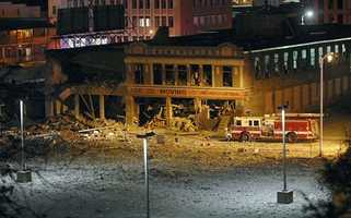 A firetruck is parked next to one of the buildings damaged in the gas explosion.
