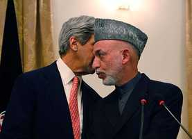Afghan President Hamid Karzai, whispers with the U.S. Sen. John Kerry, D-Mass during a press conference, in Kabul, Afghanistan on Tuesday, Oct. 20, 2009.