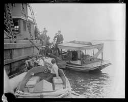 """Boat with sign """"Fresh Fish and Fruit"""" delivers bottled drinks to men on pier (possibly Prohibition selling illegal alcohol)"""