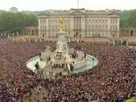 Thousands swarmed around the front of the palace for a glimpse of the royal couple.