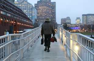 Michael Richard Smith carries a briefcase and a satchel as he walks up a gangway at a wharf in Boston