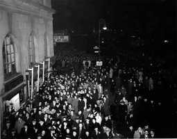 """Still in the midst of WWI and fearing bright lights could be a target, 1944's celebration happens under dimmed lights. """"For Me and My Gal"""" is playing at the Astor Theater."""