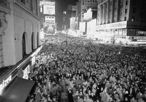 1955: Signs for Chevrolet, Canadian Club and Admiral Appliances illuminatethe crowds.