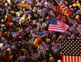 Just months after the 9/11 terror attacks, revelers wave American flags and red, white and blue decorations.