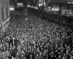 """1941. In a sign of the times, revelers are urged to """"Buy Defense Bonds"""" on a sign in the distance."""