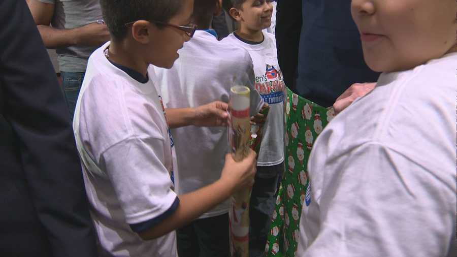 The kids were all smiles as they took the wrapping paper and covered Welker up.