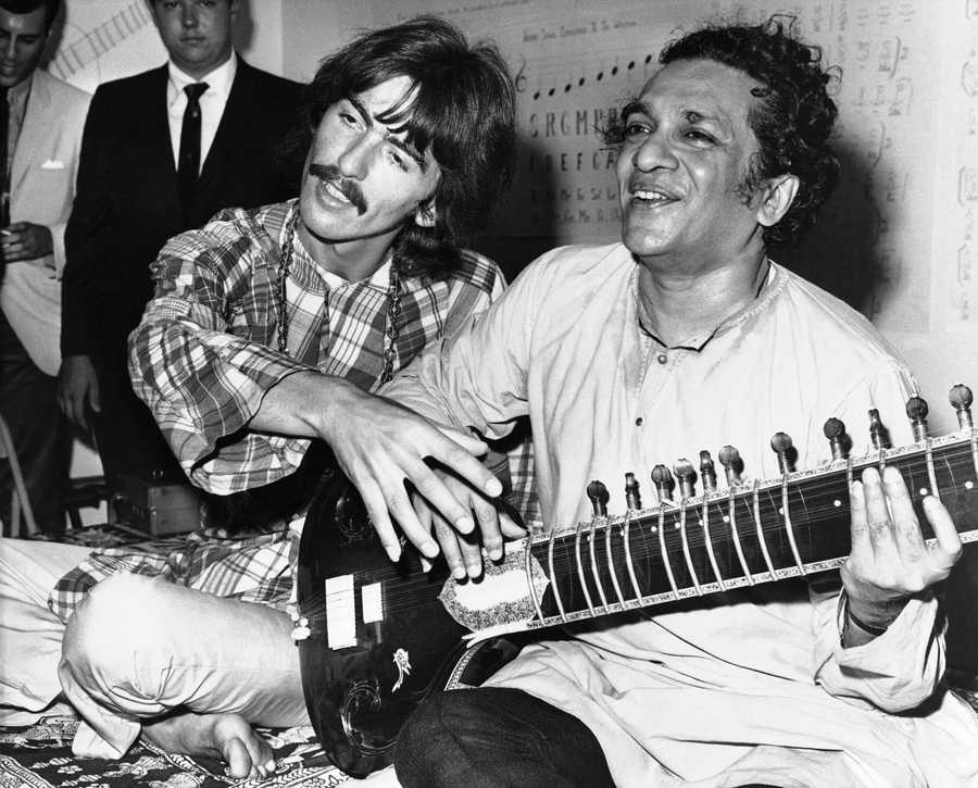 George Harrison, of the Beatles, left, sits cross-legged with his musical mentor, Ravi Shankar of India, in Los Angeles, as Harrison explains to newsmen that Shankar is teaching him to play the sitar. Shankar, the sitar virtuoso who became a hippie musical icon of the 1960s after hobnobbing with the Beatles and who introduced traditional Indian ragas to Western audiences over an eight-decade career, died Tuesday, Dec. 11, 2012. He was 92.