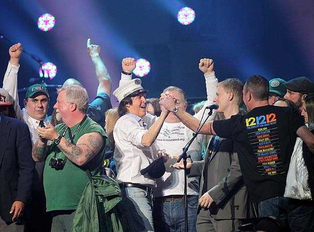 Paul McCartney, center, on stage with firefighters at the 12-12-12 The Concert