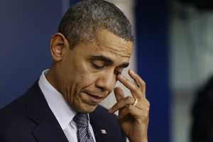 President Barack Obama wipes his eye as he speaks about the elementary school shooting in Newtown, Conn., Friday, Dec. 14, 2012, in the briefing room of the White House.