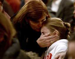 A woman comforts a young girl during a vigil service for victims of the Sandy Hook Elementary shooting, Friday, Dec. 14, 2012, at St. Rose of Lima Roman Catholic Church in Newtown, Conn.