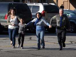 In this photo provided by the Newtown Bee, a police officer leads two women and a child from Sandy Hook Elementary School