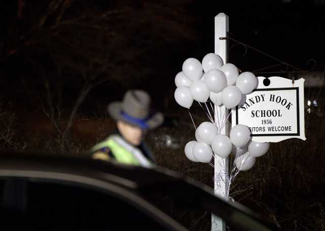 White balloons decorate the sign for the Sandy Hook Elementary School as a Connecticut State Trooper stands guard at the school's entrance.