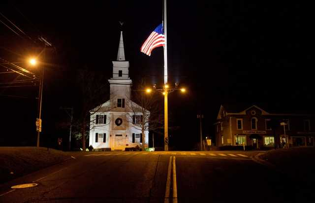 A U.S. flag flies at half-staff on Main Street in honor of the people killed when a gunman opened fire inside a Connecticut elementary school.