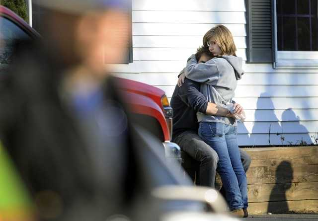 People embrace at a firehouse staging area for family around near the scene of a shooting at the Sandy Hook Elementary School in Newtown, Conn.