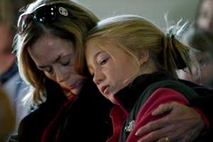 Molly Delaney, left, holds her 11-year-old daughter, Milly Delaney, during a service in honor of the victims