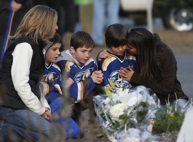 From left, Jean Bradley, Steven Turchetta, 9, Jean's son Matthew Bradley, 9, Ashton Baltes, 10, and his mother Elonda Baltes pay their respects at a memorial for shooting victims near Sandy Hook Elementary School.