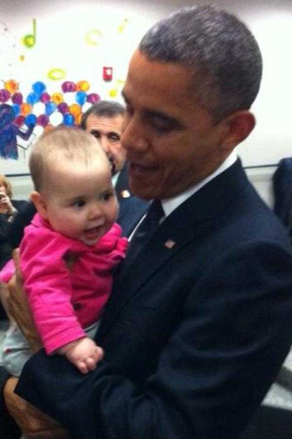 Obama holds the granddaughter of shooting victim school principal Dawn Hochsprung.