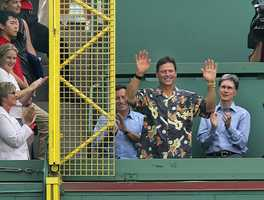 Carlton Fisk waves to fans from atop the Green Monster in left field at Fenway Park in, June 13, 2005. The Red Sox announced the left field foul pole is now named after Fisk, whose memorable World Series home run ricocheted off it 30 years ago to win Game Six of the 1975 World Series against the Cincinnati Reds. Behind Fisk are team owners Tom Werner, left, and John Henry, right.