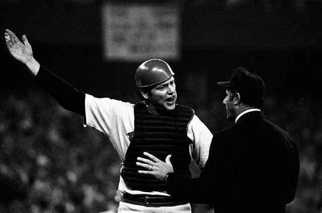 Boston catcher Carlton Fisk, left, argues with first base umpire Dick Stello that he was interfered with when Cincinnati batter Ed Armbrister brushed him at home plate as he threw to second trying to force out runner Cesar Geronimo, who eventually scored the winning run in the tenth inning of the third game of the World Series, Tuesday, Oct. 14, 1975, Cincinnati won the game 6-5.
