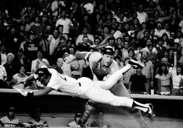 Chicago White Sox catcher Carlton Fisk, back center, pulls back after tagging a diving New York Yankees Bobby Meacham out at the plate in the seventh inning at Yankees Stadium, Friday, Aug. 3, 1985. Seconds later Fisk made it a double play with a second put out as Dale Berra tried to score right behind Meacham both runners tried to score on a single by Rickey Henderson. White Sox won 6-5 in eleven innings.
