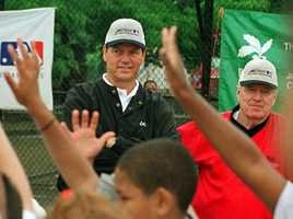Carlton Fisk, center, responds to questions from children, front, as former Red Sox manager Joe Morgan, right, looks on during a youth baseball clinic in Boston's Dorchester section on July 1, 1999. Nearly a hundred kids from around Massachusetts participated in the program.