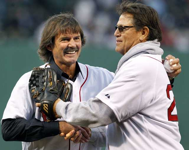 Boston Red Sox legends, pitcher Dennis Eckersley, left, and catcher Carlton Fisk shake hands after participating in the honorary first pitch prior to an interleague baseball game against the Chicago Cubs at Fenway Park on Friday, May 20, 2011.