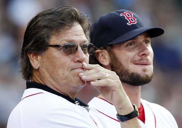 Carlton Fisk, left, watches a presentation on the scoreboard next to Red Sox's Jarrod Saltalamacchia before throwing out the ceremonial first pitch before a baseball game against the Tampa Bay Rays, Saturday, May 26, 2012.