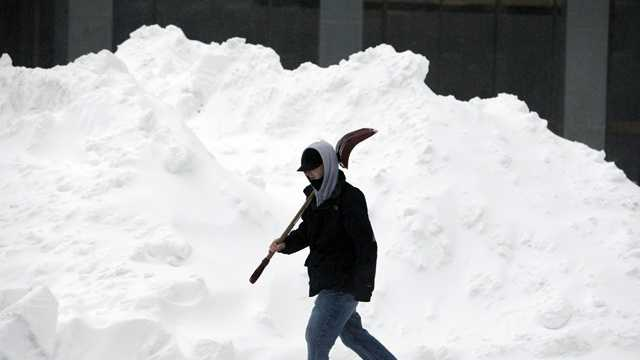 Snow man with shovel walks by huge drift.jpg