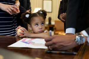 May 25, 2012 -- Luz Graham-Urquilla, 4, watches as the President signs her drawing at the Resolute Desk in the Oval Office.""