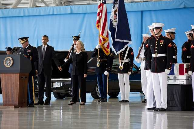 Sept. 14, 2012 The President grasps the hand of the Secretary of State after his remarks during the ceremony at Joint Base Andrews, marking the return to the United States of the remains of J. Christopher Stevens, U.S. Ambassador to Libya&#x3B; Sean Smith, Information Management Officer&#x3B; and Security Personnel Glen Doherty and Tyrone Woods, who were killed in the attack on the U.S. Consulate in Benghazi, Libya.