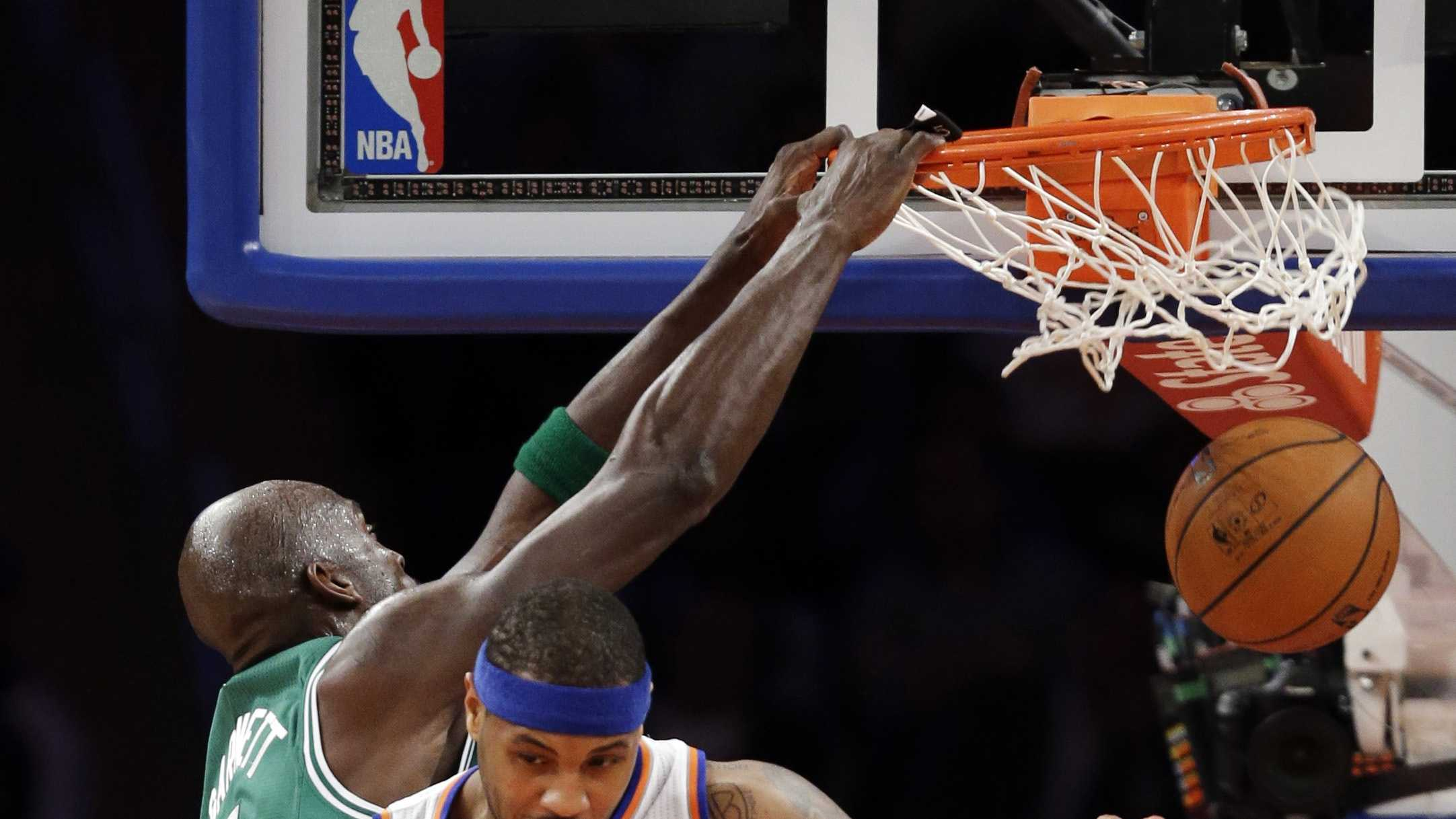 Kevin Garnett dunks against New York Knicks forward Carmelo Anthony in the first half of their NBA basketball game at Madison Square Garden in New York, Monday, Jan. 7, 2013.