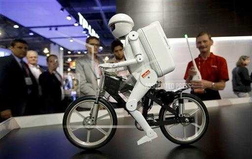 Murata Boy, a bicycle riding robot, rides a bike at the Murata booth.