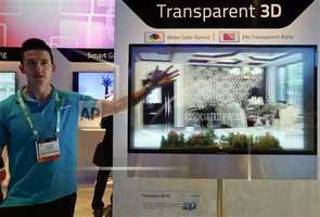 Payton Tyrell, left, demonstrates on a transparent 3D TV at the Hisense booth.